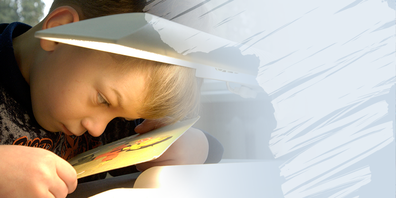 Child with low vision observing a drawing under a white light